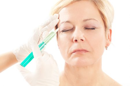 a woman getting a botox injecton to her forehead