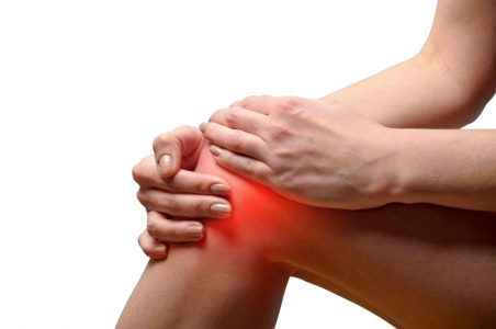 a person holding her knee from pain with both hands