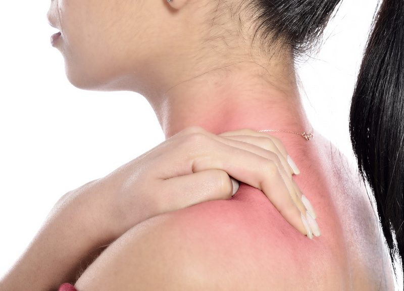 a woman is holding her arm in pain