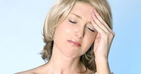 a woman holding hear forehead because of a tension headache