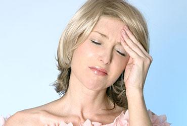 a woman holding hear forehead because of a tension headache