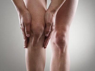 a person holding his knee form pain with both hands