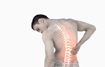 Man holding his lower back, his back is x-rayed